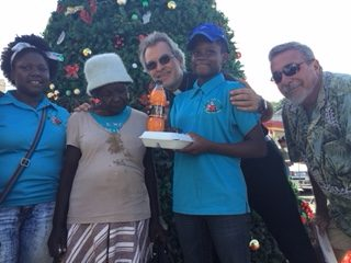 Father Samuel distributing a Christmas Dinner to the indigent Accompanied buy our Church Council President and a member of the Youth Oratory